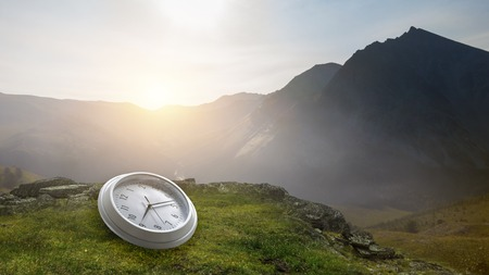Clock on the ground with mountain landscape view