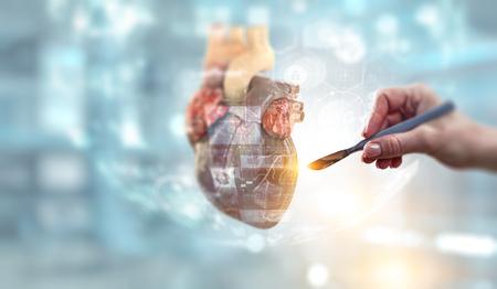 Female doctor hand with scalpel beside anatomic heart model. Mixed media Stockfoto