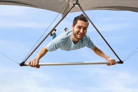 Junger Mann fliegt auf Drachenflieger. Gemischte Medien