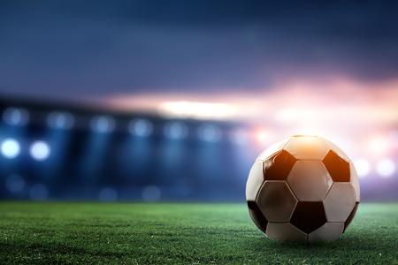 Arène de football de nuit complète dans les lumières avec ballon en gros plan