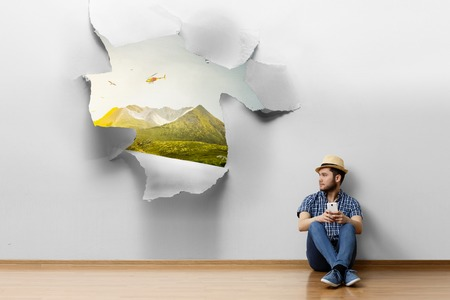 Young man sitting on the floor, a moment for relax concept. Mixed media Stockfoto