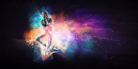Modern female dancer jumping in hoodie with colourful splashes background. Mixed media Banque d'images - 123587637