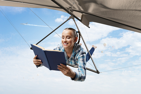 Young woman flying on hang glider. Mixed media Stock Photo - 123588008