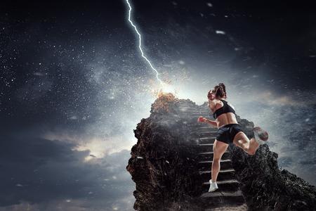 Sports woman running on stone ladder. Mixed media Stock Photo