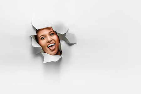 Woman looking out from a hole of torn paper Stockfoto