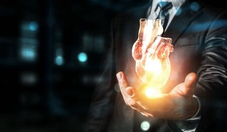 Man`s hands showing anatomical heart model. Mixed media.