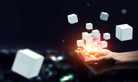 Man`s hand and cubes levitating above. Mixed media Banco de Imagens
