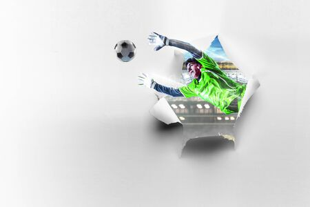 Paper breakthrough hole effect and soccer player. Mixed media Stockfoto