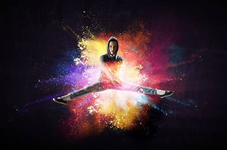 Modern female dancer jumping in hoodie with colourful splashes background. Mixed media Banque d'images - 124475630