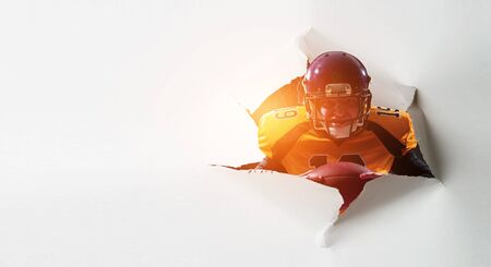 Paper breakthrough hole effect and football player. Mixed media
