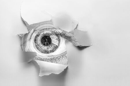 Eye in a hole of torn paper Stockfoto