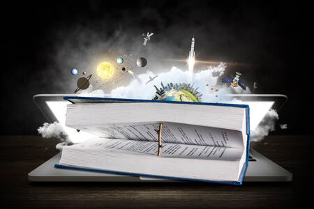 Open book with wooden natural bookmark lying on laptop, space background