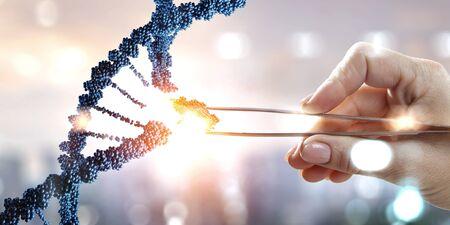 DNA-Moleküle entwerfen mit weiblicher Hand, die Zangen hält. Gemischte Medien Standard-Bild