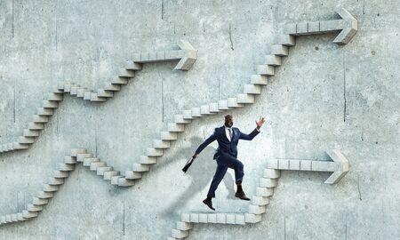 Black businessman climbing stone stairs illustrating career development and success concept. Mixed media Фото со стока