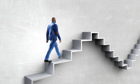 Black businessman climbing stone stairs illustrating career development and success concept. Mixed media Zdjęcie Seryjne