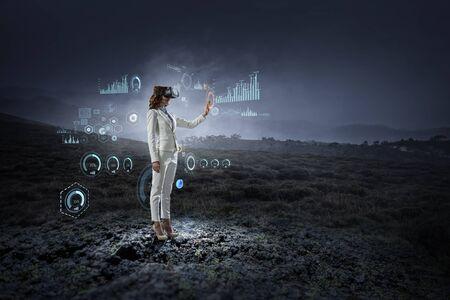 Young female in virtual reality. Mixed media Фото со стока