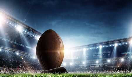Night football arena in lights with a ball close up Stock Photo