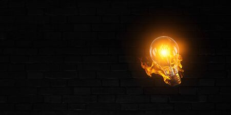 Classic Edison light bulb on black brick background