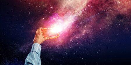 Businessman`s hand holding a small magic paper box, mixed media