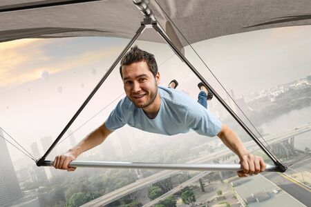 Young man flying on hang glider. Mixed media Stock Photo