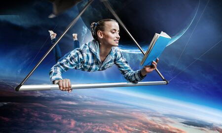 Young woman flying on hang glider. Mixed media