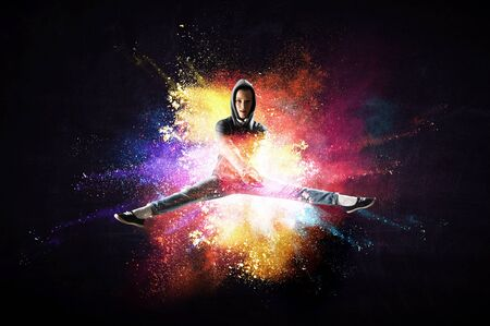 Modern female dancer jumping in hoodie with colourful splashes background. Mixed media Banque d'images - 125852537