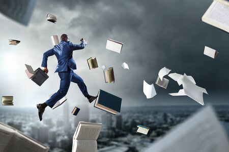Back view of black businessman with briefcase running among flying books and papers on dark cloudy cityscape urban background