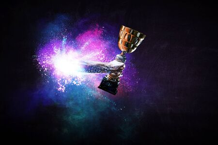 Hands holding champion cup on colourful splashes background. Mixed media Stock Photo