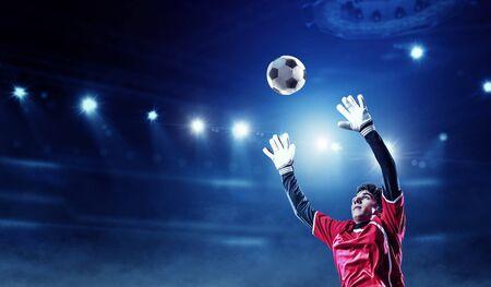 Jugador de fútbol en el estadio en acción. Técnica mixta Foto de archivo