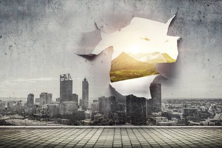 A hole in a sheet of paper with city view. Mixed media Stockfoto