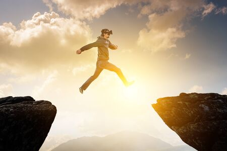Young man in VR jumping over precipice. Mixed media