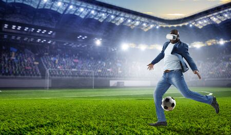 Virtual Reality headset on a black male playing football. Mixed media Stock Photo