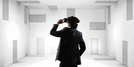 Back view of a young businessman in virtual reality headset in a room with lots of doors. Mixed media