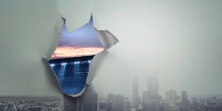 A hole in a sheet of paper with stadium view Stockfoto