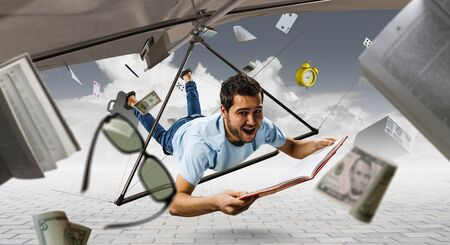 Young man flying on hang glider. Mixed media Фото со стока