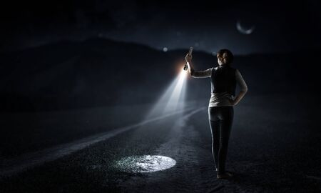 Young woman holding a flashlight