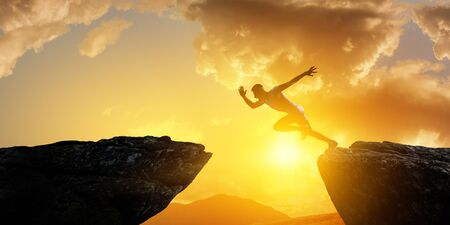 Jumping over precipice, challenge concept. Foto de archivo - 127247959