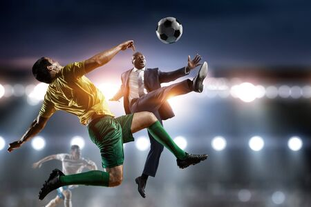 Black businessman playing footbal on a satdium Stock Photo