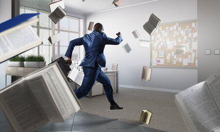 Running black businessman with briefcase