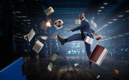 Black businessman in a suit playing footbal Stock Photo