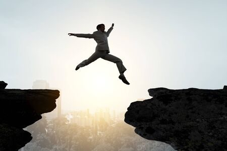 Jumping over precipice, challenge concept. Standard-Bild - 127831057