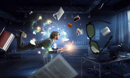 El hombre vuela y trabaja en la computadora portátil. Técnica mixta Foto de archivo