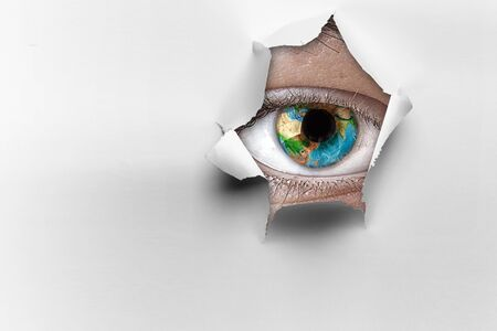 Eye in a hole of torn paper