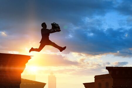 Jumping over precipice, challenge concept. Standard-Bild - 128605754