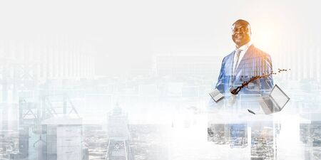 Smiling black businessman standing surrounded with office objects and cityscape background