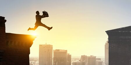 Jumping over precipice, challenge concept. Standard-Bild - 128605851