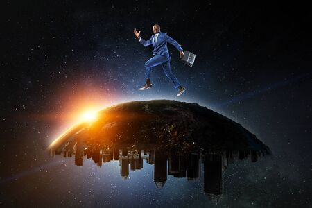 Black businessman running on the Globe with city buildings on the starry space background Reklamní fotografie