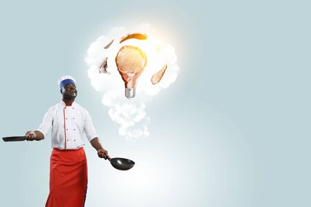 Black chef creative cooking. Mixed media. Stock Photo