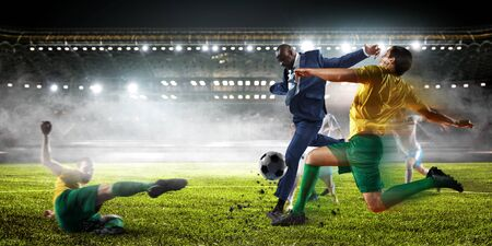 Soccer man in action with ball. Mixed media Stock Photo
