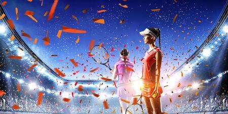 Young women playing tennis on stadium